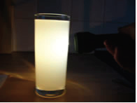a torch shining through water in a glass